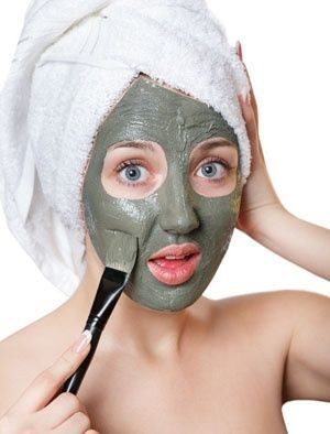 Woman applying a facial mud mask.
